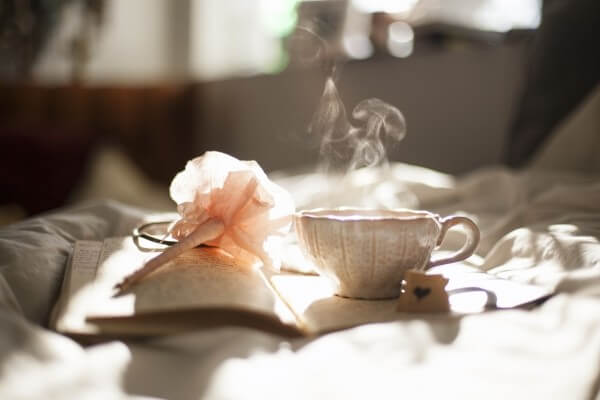 tea-cup-pen-and-diary-on-bed
