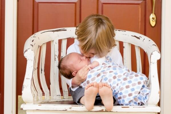 brother-sitting-in-wooden-chair-holding-hid-baby-sister